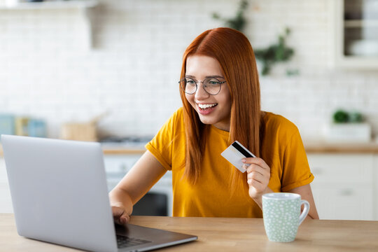 Young cheerful caucasian girl doing online shopping at home using laptop computer and credit card, redhead beautiful girl making profitable purchases in the Internet