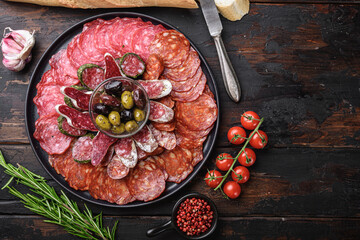 Fototapeta Cured meat platter of traditional spanish tapas. Chorizo, salchichon, longaniza and fuet on dark wooden background, topview with space for text obraz