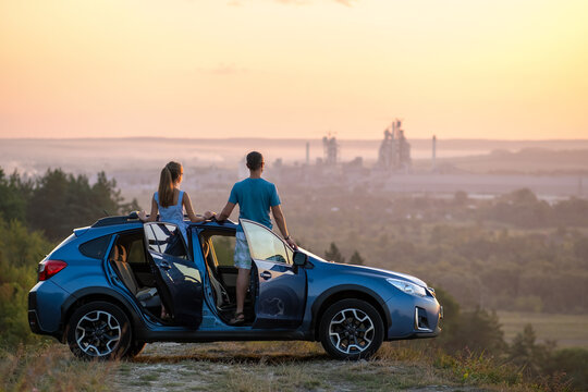 Happy couple standing near their car at sunset. Young man and woman enjoying time together travelling by vehicle.