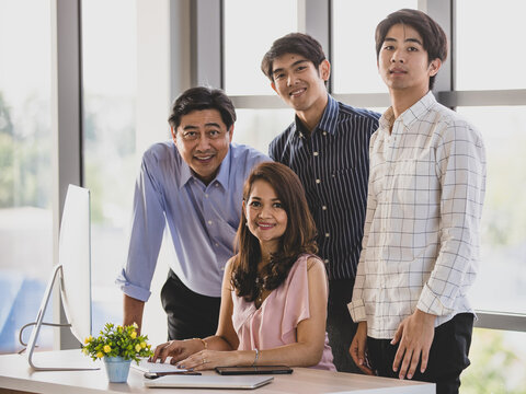 Close up and Portrait wealthy successful Asian business Family looking at camera, smiling confidently, proudly and happy while sitting, working and using computer in comfortable office during the day.