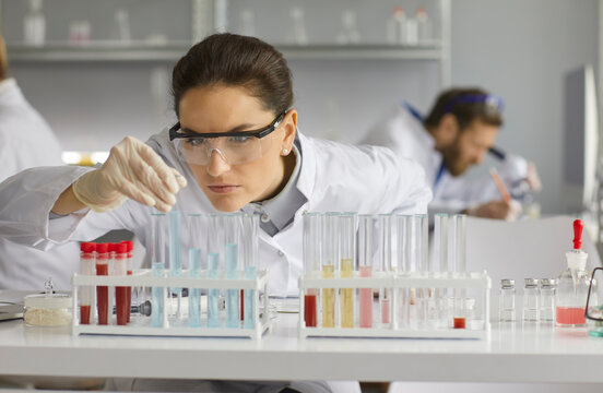 Portrait of focused female scientist in her workplace in modern medical science laboratory. Serious concentrated chemist leaning over lab table and working with glass tubes full of different liquids