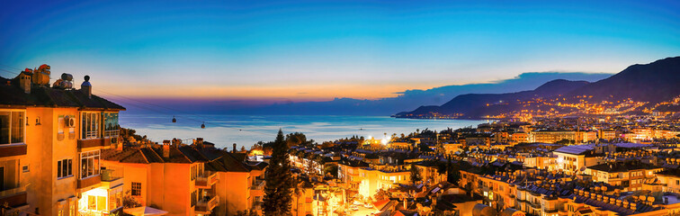 Wide-format image of Turkish resort of Alanya - beautiful evening sky with reflection in water of bay, silhouette of mountains with scattering of lights and bright evening city, aerial photo.