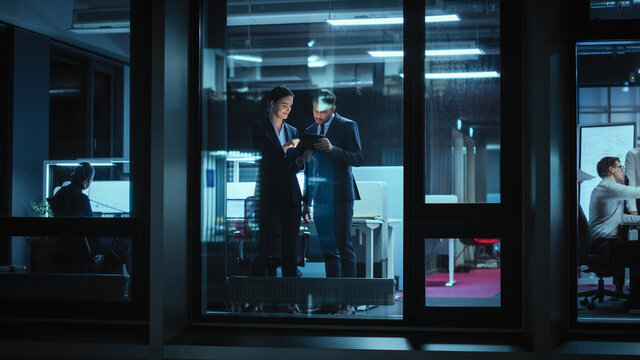 Shot from Outside: Businesswoman and Businessman in a Suit Working on a Tablet Computer in the Office. Manager Standing by the Window. Partners Chat about Financial and Business Development.