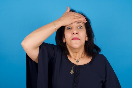 Oops, what did I do? middle aged Arab woman standing against blue background holding hand on forehead with frightened and regret expression.