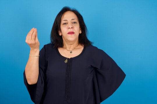What the hell are you talking about. Shot of frustrated middle aged Arab woman gesturing with raised hand doing Italian gesture, frowning, being displeased and confused with dumb question.