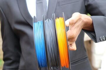 Fototapeta Businessman showing 3D printer filament made from renewable resources. Different colors PLA filament for 3D printer made from bio plastic obraz