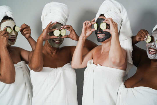 Multigenerational women having fun wearing face beauty mask with cucumbers on their eyes - Skin care therapy - Main focus on caucasian female face