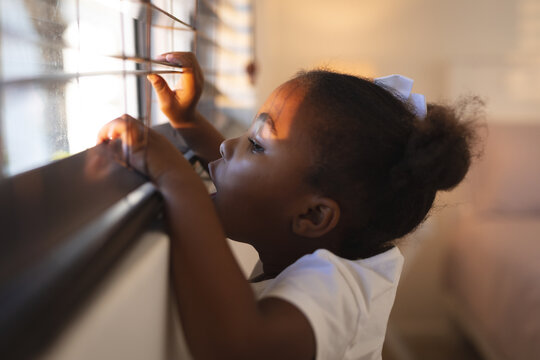 Curious african american girl standing and peering through window blinds on a sunny day