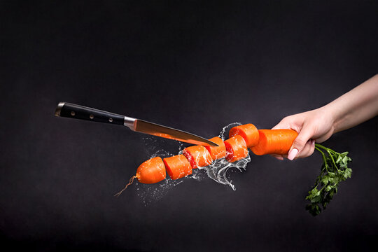 Whole and sliced ripe carrots levitate on a black background Levitating knife cuts carrots Still life with carrots