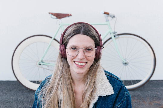 Cheerful woman listening to music near bicycle