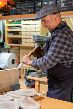 Professional carpenter with hammer and chisel working in workshop