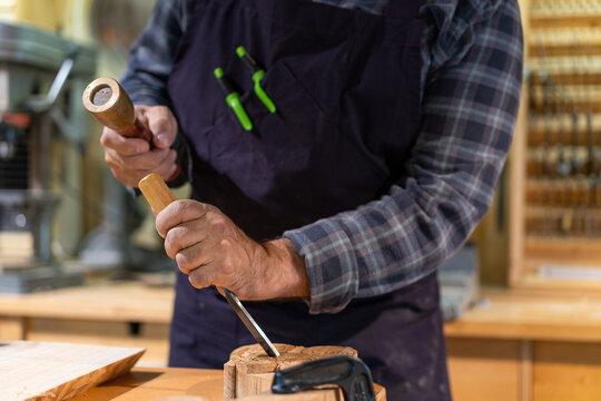 Craftsman carving wooden detail in workshop