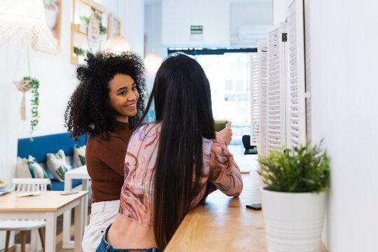 Cheerful diverse women drinking smoothie in bar