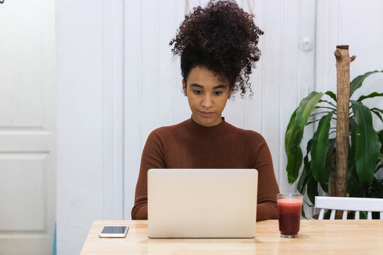 Black woman working on laptop in cafe