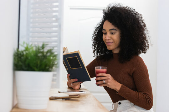 African American woman drinking smoothie and reading book in bar