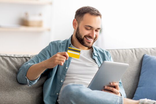 Positive guy with credit card and tablet pc sitting on sofa at home, making online order, purchasing goods on internet