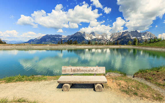 Famous wooden bench Lieblingsplatzl at the Astbergsee lake on the Astbergalm in Going at the Wilder Kaiser mountains