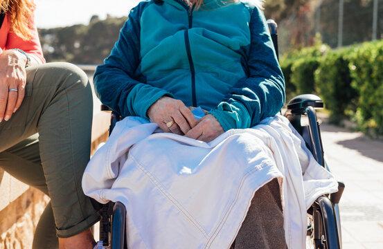 Crop caregiver sitting aged woman in wheelchair
