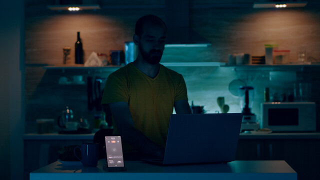 Man working from house with automation lighting system, sitting in kitchen turning on the lights using voice command to smart home application on smartphone. Person monitoring light with wifi gadget