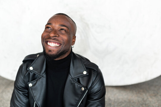 Cheerful black man smiling looking up