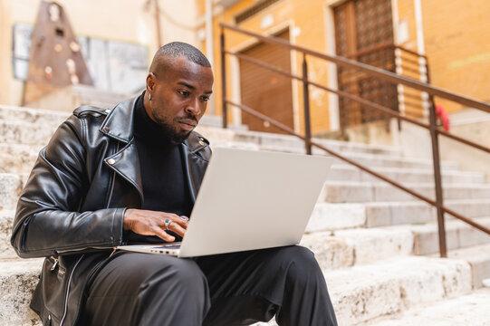 Focused black man using laptop on street staircase