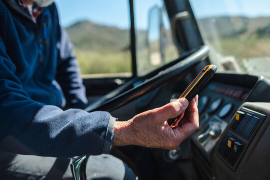 Senior male driver using smartphone in van