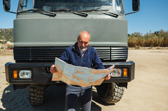 Concentrated travelling man reading map near car