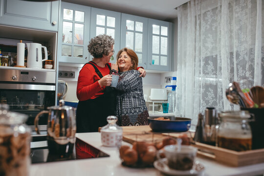 Cheerful couple of lesbians embracing in house kitchen