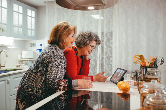 Grandmother lesbian couple having video call on tablet in kitchen