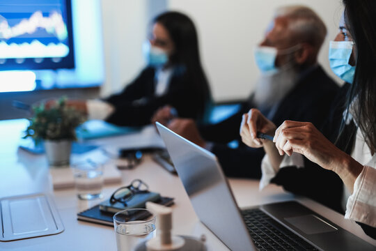 Business trader team making stock crypto market analysis inside hedge fund office wearing safety masks - Main focus on woman left hand