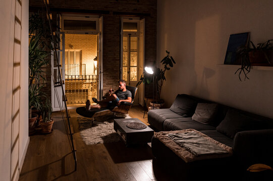 Man resting in evening with glass of wine