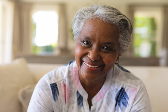 Portrait of senior african american woman sitting on sofa looking at camera and smiling
