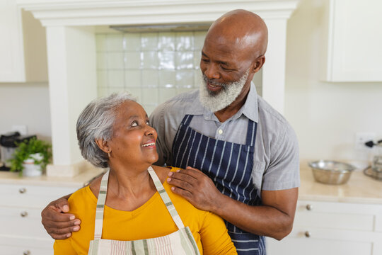 Senior african american couple in kitchen looking at each other and smiling