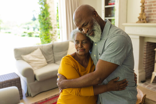 Senior african american couple embracing with eyes closed in living room