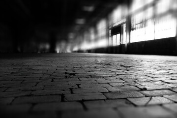 Dimly lit abandoned factory shot from low angle with limited depth of foucs in black and white