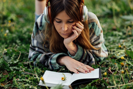 Woman in headphones reading book on grass