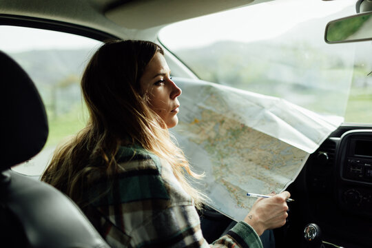 Driver with map in car during trip