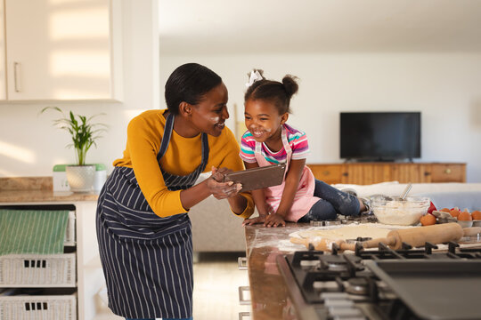 Smiling african american mother and daughter baking in kitchen looking at recipe on tablet