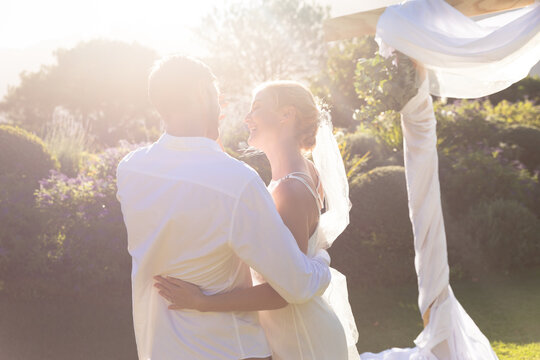 Happy caucasian bride and groom getting married and embracing