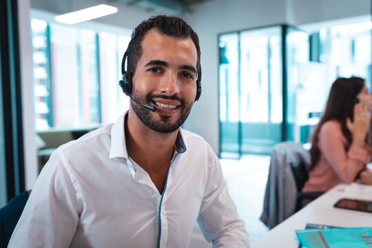 Portrait of mixed race businessman wearing headset and sitting at table smiling