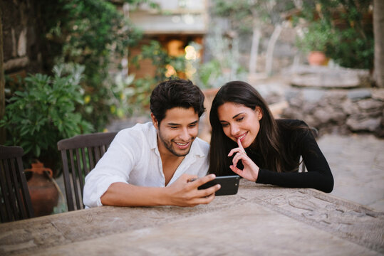 young couple looking at mobile while having fun