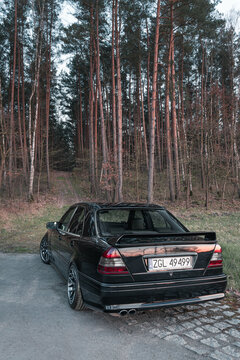 Goleniow, Poland - April 20th, 2021: Old black tuned Mercedes Benz C-class (W202 model) near forest. Compact luxury sedan icon from the 90s. Vertical orientation