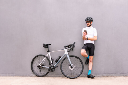 Bicyclist with smartphone against modern bike on gray background