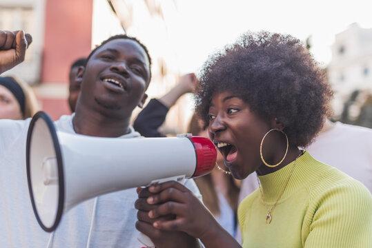 Black woman screaming in loudspeaker during demonstration in city