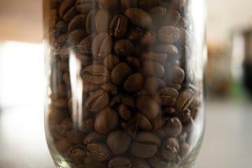 Gros plan sur des grains de café dans un bocal en verre.