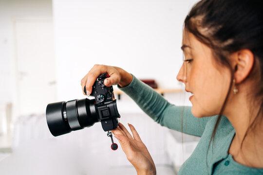 Photographer with photo camera on light background