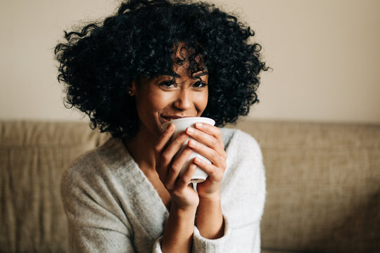 Happy black woman sitting on sofa and looking at camera
