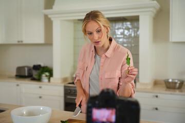 Caucasian woman in kitchen preparing food, holding salad leaf to camera, making cooking vlog