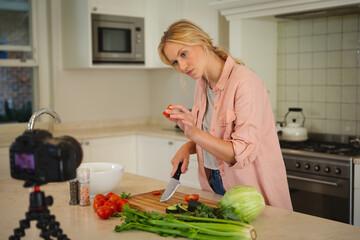 Caucasian woman in kitchen preparing food, holding vegetable to camera, making cooking vlog