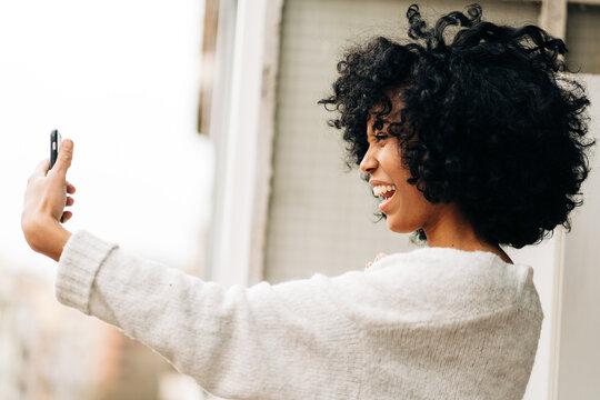 Positive ethnic woman taking selfie on balcony